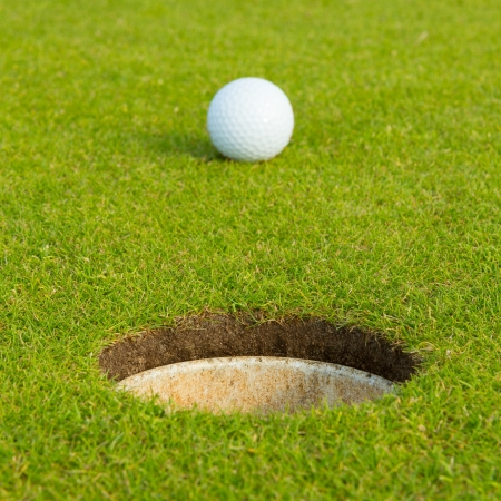 hole in one: Golf ball on a green, in front of the hole, focus on the hole