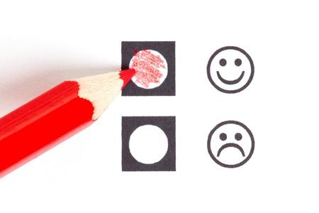 Crayon rouge en choisissant le droit smiley (humeur) Banque d'images