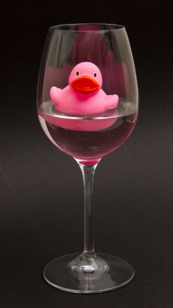 Pink rubber duck in a wineglass with water (black background) photo