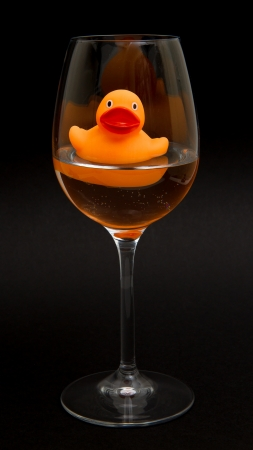 Orange rubber duck in a wineglass with water (black background) photo