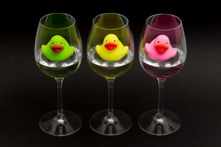 PATO: Verde, amarillo y rosa patos de goma en copas de vino, fondo oscuro