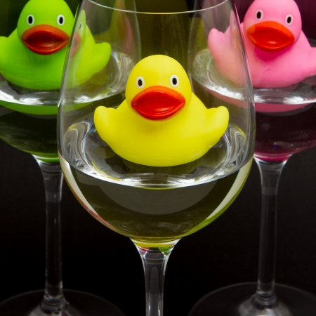 Green, yellow and pink rubber ducks in wineglasses, dark background