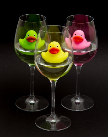 rubber ducky: Green, yellow and pink rubber ducks in wineglasses, dark background