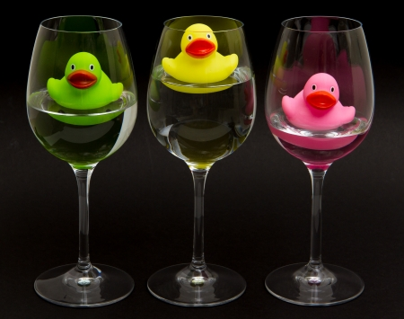 Green, yellow and pink rubber ducks in wineglasses, dark background photo