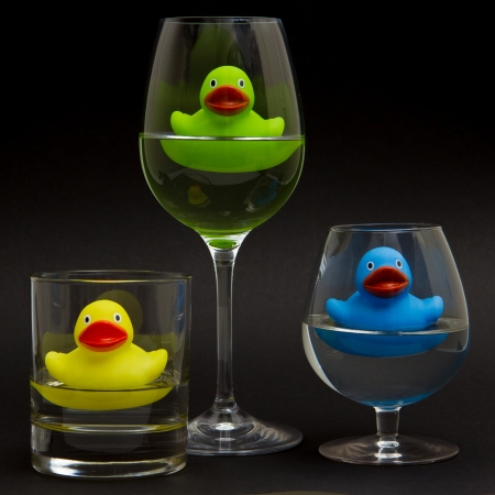 Green, yellow and blue rubber duck in different glasses on a dark background photo
