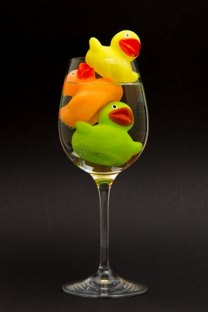 Yellow, orange and green rubber duck in a wineglass with water (black background) photo