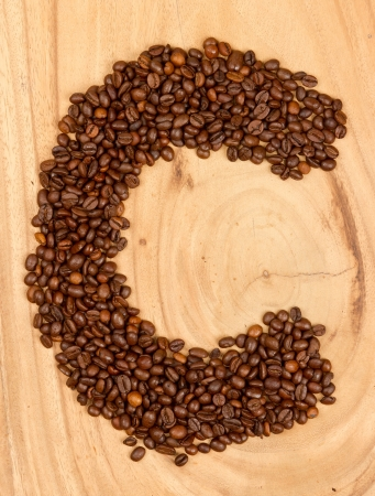 Letter C, alphabet from coffee beans. isolated on wood photo