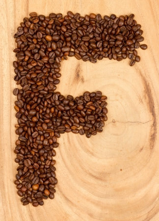 Letter F, alphabet from coffee beans. isolated on wood photo