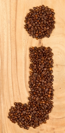 Letter J, alphabet from coffee beans. isolated on wood photo