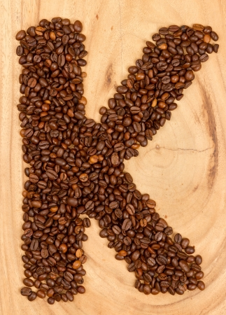 Letter K, alphabet from coffee beans. isolated on wood photo