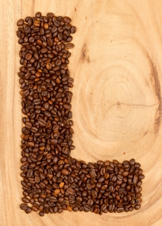 Letter L, alphabet from coffee beans. isolated on wood photo
