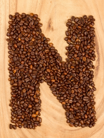 Letter N, alphabet from coffee beans. isolated on wood photo