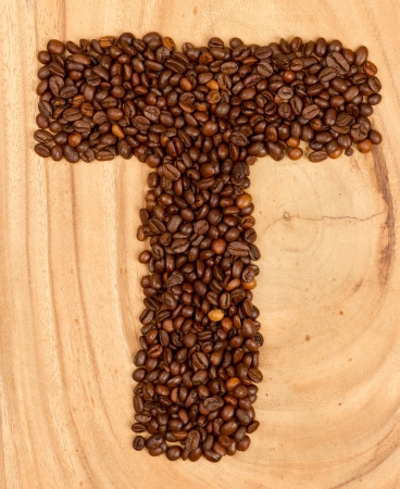 Letter T, alphabet from coffee beans. isolated on wood photo