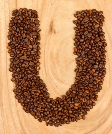 Letter U, alphabet from coffee beans. isolated on wood photo