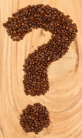 Question mark from coffee beans, isolated on wood photo