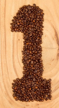 Number from coffee beans, isolated on wood photo