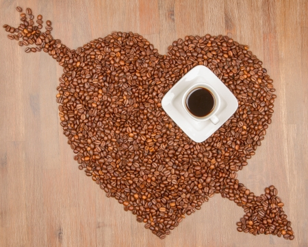 coffe beans: Coffe beans in the shape of a big heart, isolated on wood