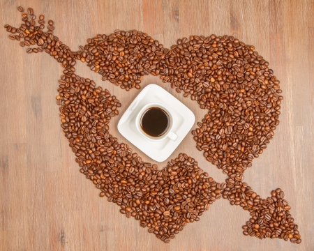 Coffe beans in the shape of a big heart, isolated on wood photo