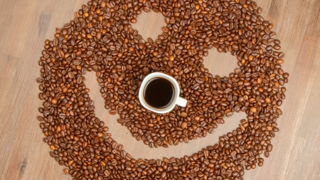 Coffee grains arranged in smiley. Isolated on wooden background. photo