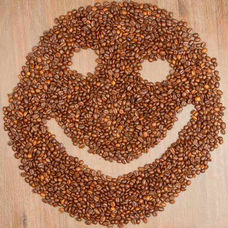 breakfast smiley face: Coffee grains arranged in smiley. Isolated on wooden background.