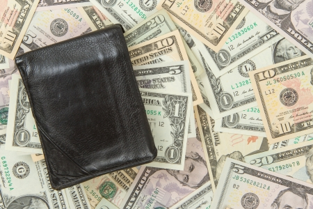 Old used wallet with dollars isolated on dollar bills Stock Photo - 14431134
