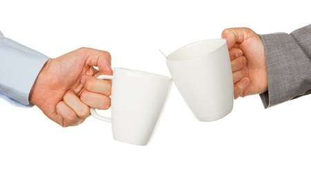 Close-up of two business partners hands holding cups of coffee