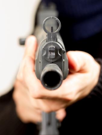 Photo de terroriste avec un pistolet attaquer quelqu'un tout en pointant vers l'avant