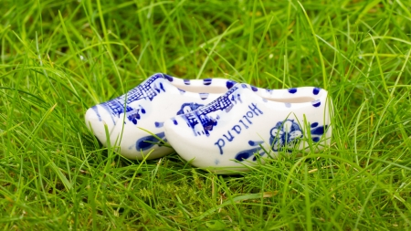 Pair of small porcelain clogs from Holland, isolated in grass photo