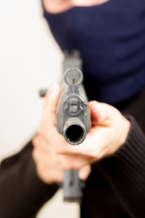 Photo of terrorist with gun attacking someone while pointing it forwards photo