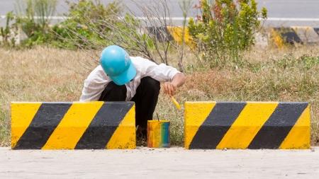 roadworks: Man painting roadworks barriers on a road in Vietnam, Highway 1