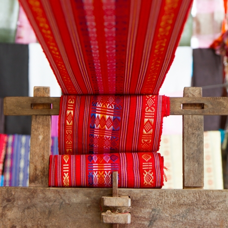 the textile industry: Handmade silk textile industry, silk scarf on a old machine (Vietnam)