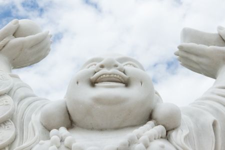 buddha face: Laughing Buddha isolated against the bright sky