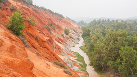 covert: Ham Tien canyon in Vietnam, small stream carving through the sand, covert in fog