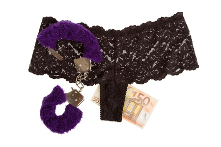 Fluffy purple handcuffs, panties and money on a white background, prostitution Stock Photo - 15247170