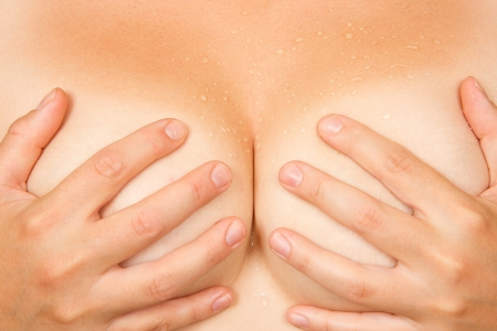 Sweaty partie supérieure du corps de la femme, les mains couvrant les seins Banque d'images