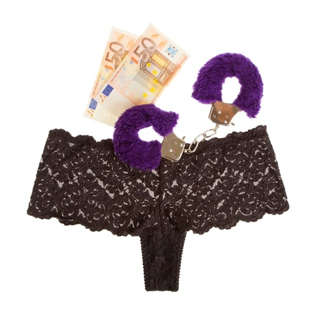Fluffy purple handcuffs, panties and money on a white background, prostitution Stock Photo - 15310960