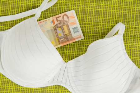 Lingerie with money on green bed sheets