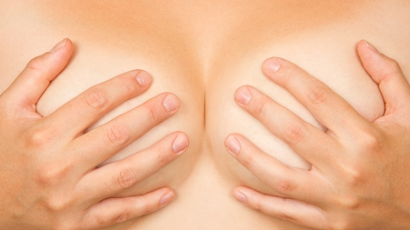Upper part of female body, hands covering breasts Stock Photo