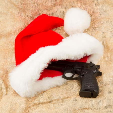 concealed: Weapon (firearm) concealed in santas hat, isolated on canvas