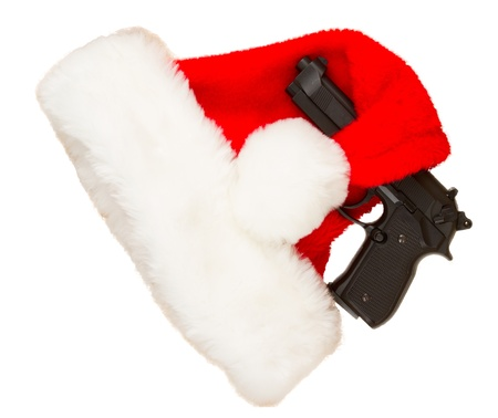 concealed: Weapon (firearm) concealed in santas hat, isolated on white