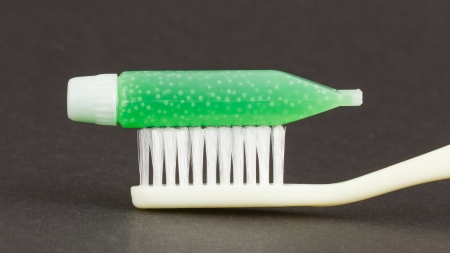 Toothbrush and green toothpaste isolated on a grey background photo
