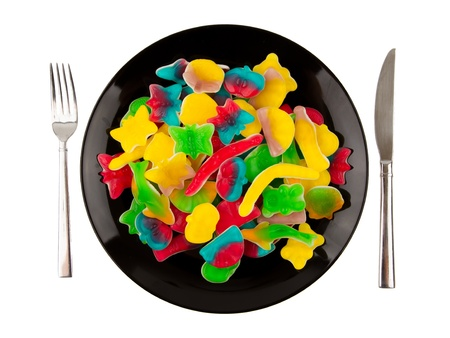 butterfly knife: Colorful candies in many different shapes isolated on a black plate, isolated on white