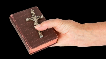 christus: Old hand  woman  holding a very old bible, isolated on white