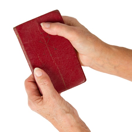 Old hands  woman  holding a very old bible, isolated on white photo
