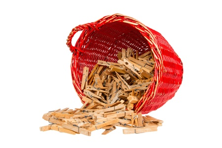 Very old red basket with wooden clothespins, isolated photo