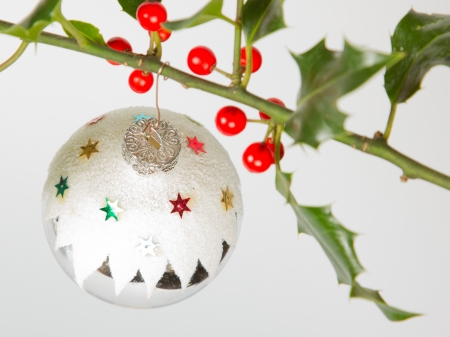 Very old silver christmas ball hanging from a twig (butchers broom), isolated photo
