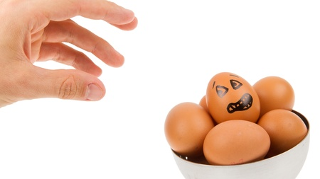Scared egg, waiting to be grabbed by a hand, isolated photo