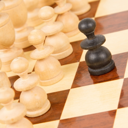 battle plan: Black pawn on a wooden chessboard, old handcarved set