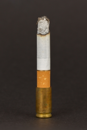 Burning cigarette in an old tin ashtray, isolated Stock Photo - 16552264