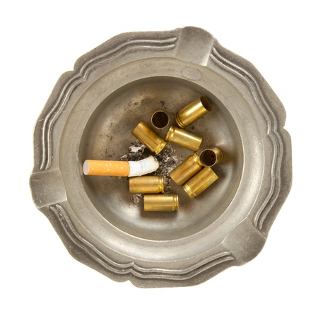 fag: Burning cigarette and empty 9mm bullet casings in an old tin ashtray, isolated Stock Photo